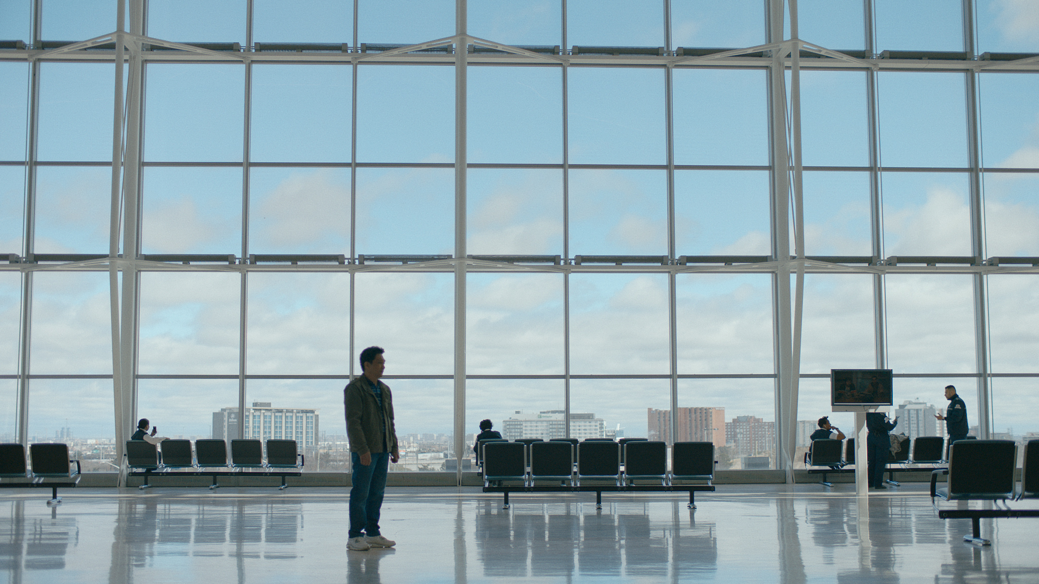 A film still from Islands of a man standing alone in a bright airport terminal in front of a large window. He has black hair and tan skin.